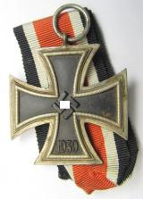 Iron Cross 2nd class (or: 'EK II. Klasse') being a non-maker-marked example that comes together with its original (somewhat orange-red-coloured) ribbon (ie. 'Bandabschnitt') as was produced by the desirable 'C.E. Junckers'-company
