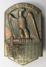 Commemorative, tin-based- and/or: golden-bronze-coloured (I deem) N.S.D.A.P.-related 'tinnie' depicting an eagle-device resting on a sword and that is entitled: 'Stirb und Werde - Schlageterkundgebung - Düsseldorf - 26.27.5.1934'