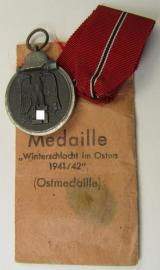 Medal-set: 'Winterschlacht im Osten 1941-42' being a maker- (ie. '25'-) marked specimen by the maker- (ie. 'Hersteller') named: 'AG der Graveur-, Gold- und Silberschmiede-Innungen' and that comes packed in its original pouch of issue