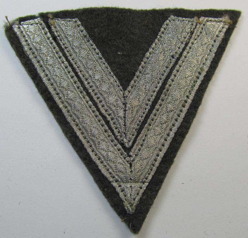 WH (Heeres) 'Armwinkel' (ie: arm rank-chevron) as executed on 'smooth'-type, field-grey-coloured wool as was intended for usage by a soldier with the rank of: 'Obergefreiter'