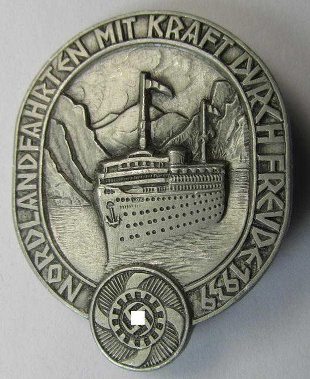 Attractive, 'KdF'- (ie. 'DAF-/Kraft durch Freude'-) related day-badge (ie. 'tinnie') as was issued to commemorate the  Scandinavian-trips and depicting a KDF-vessel and text: 'Nordlandfahrten mit Kraft durch Freude 1939'